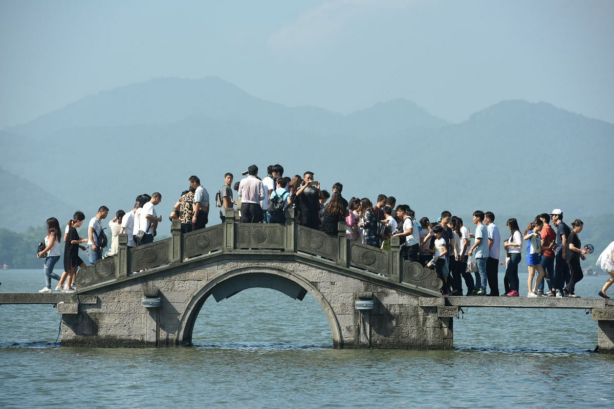 Visitors walk on a bridge on West Lake during China's Golden Week holiday in Hangzhou, Zhejiang Province, China, on Oct 2, 2016.