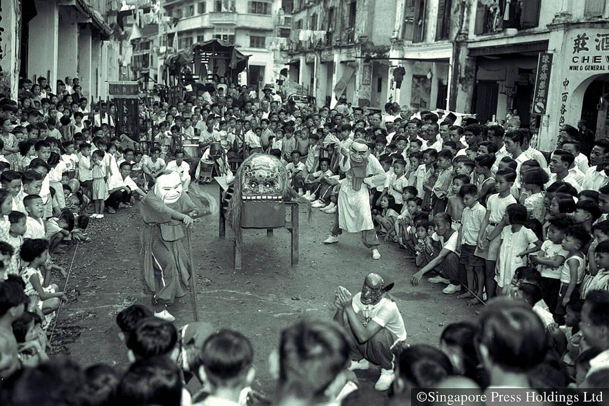1954: A lion dance in McCallum Street, featuring big-headed dolls, is a big draw for many, especially children.