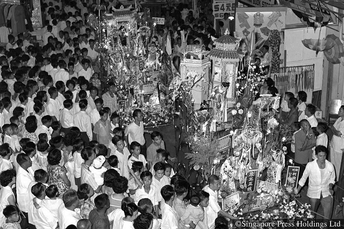 1963: Events held on the last day of Chinese New Year, Chap Goh Mei, are well attended. Here, a large crowd gathers to watch a Chap Goh Mei procession in Geylang.