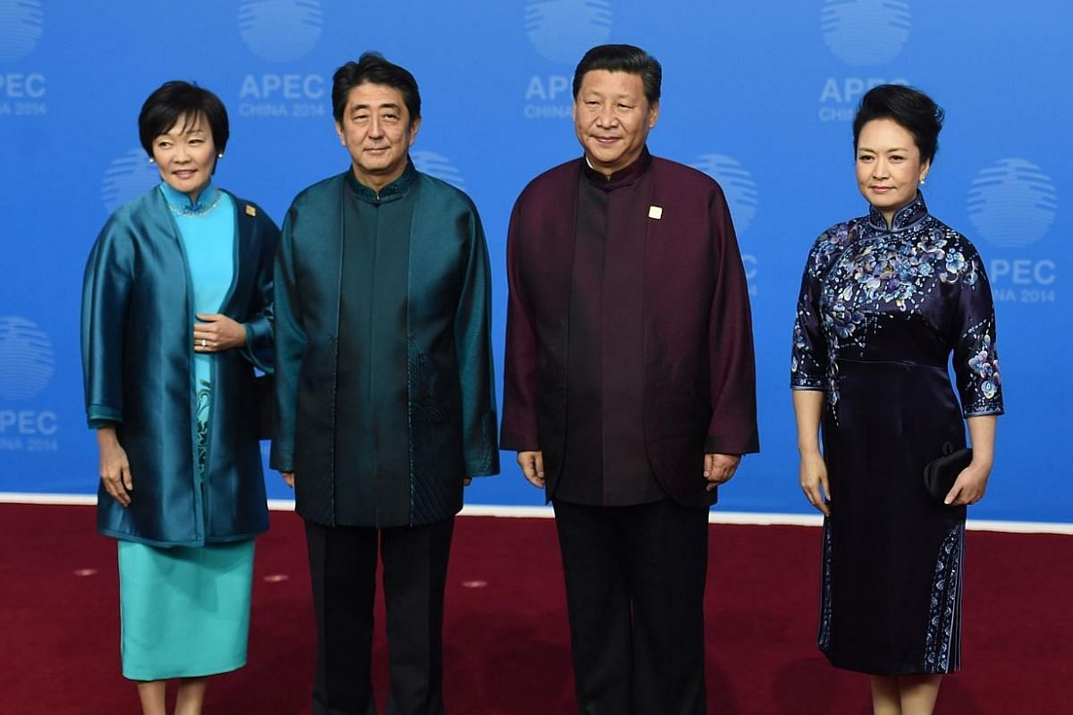Japan's Prime Minister Shinzo Abe and his wife Akie (left) pose for a photo with Chinese President Xi Jinping and his wife Peng Liyuan as they arrive for the Asia-Pacific Economic Cooperation (APEC) Summit banquet at the National Aquatics Center in t