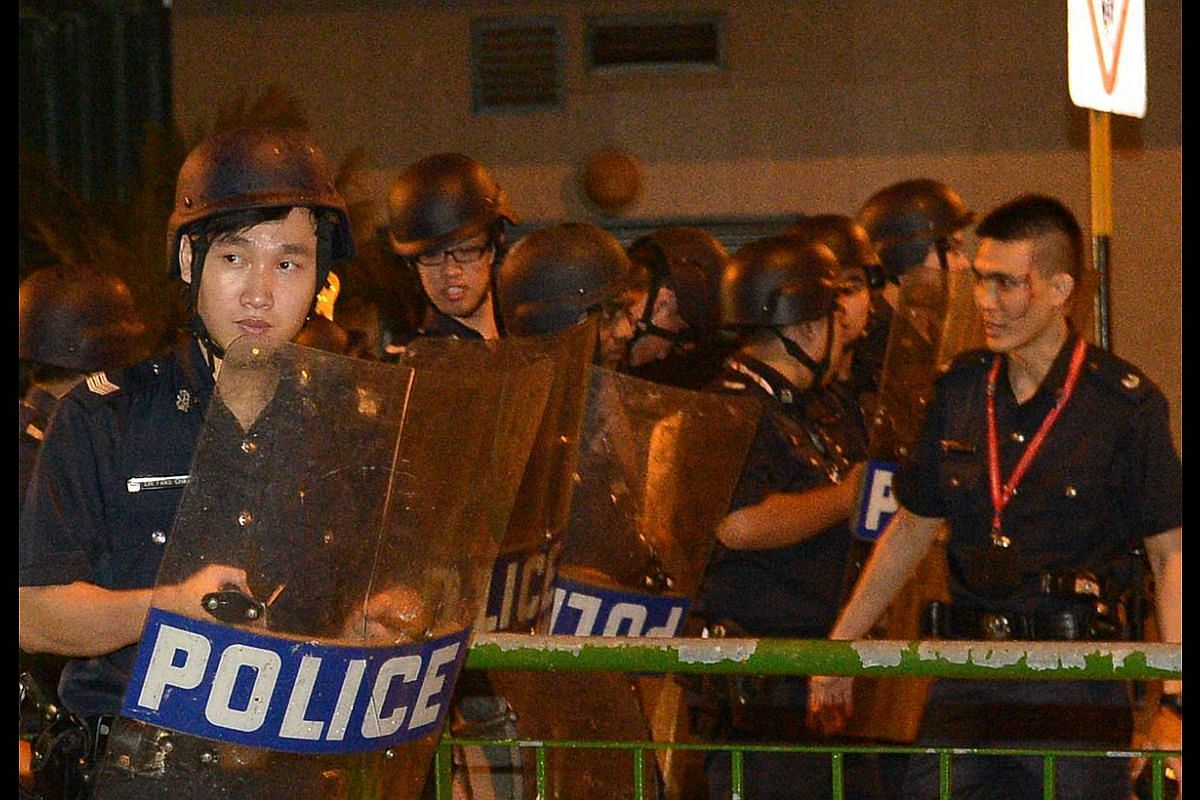 Police – one of them injured – at the scene of the riot in Race Course Road last December. The police will further review capabilities, training and equipment that front-line officers need. -- ST PHOTO: DESMOND WEE