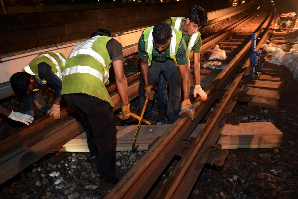 Maintenance staff replacing the wooden sleepers on the train tracks. SMRT has replaced all the rail sleepers on the North-South Line.
