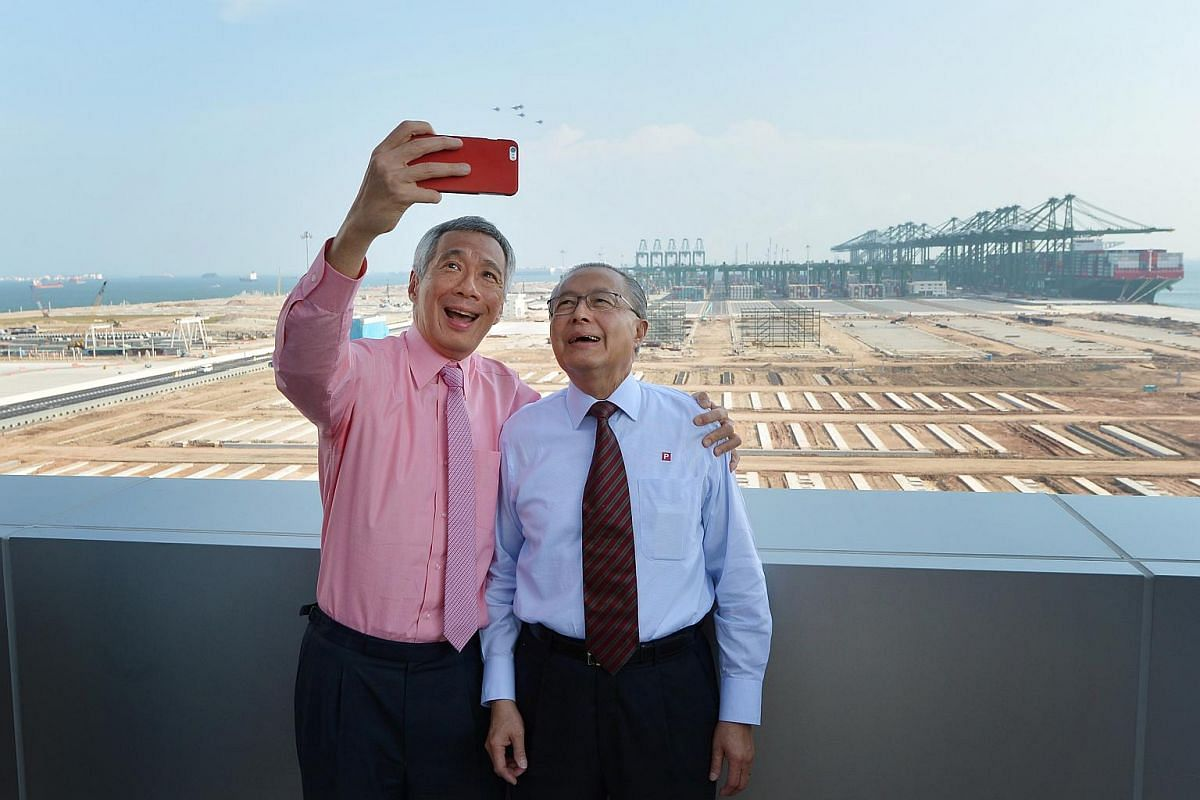 PM Lee (left) taking a selfie with PSA Group Chairman Fock Siew Wah against the backdrop of the Phase 3 and 4 expansion of Pasir Panjang Terminal.