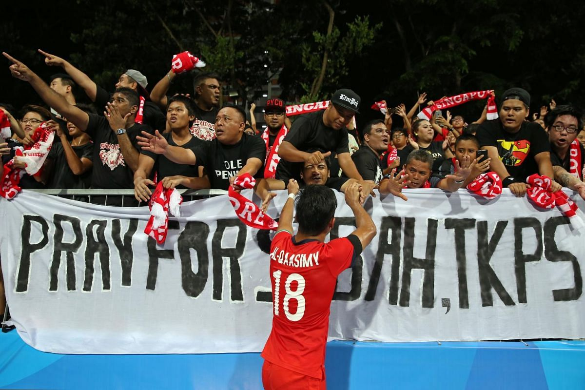 Singapore footballer Muhammad Al-Qaasimy acknowledging fans in front of a banner put up for the victims of the Sabah earthquake, after Singapore beat Cambodia 3-0 on 8 June 2015, in the Group A match of the 28th SEA Games football competition.