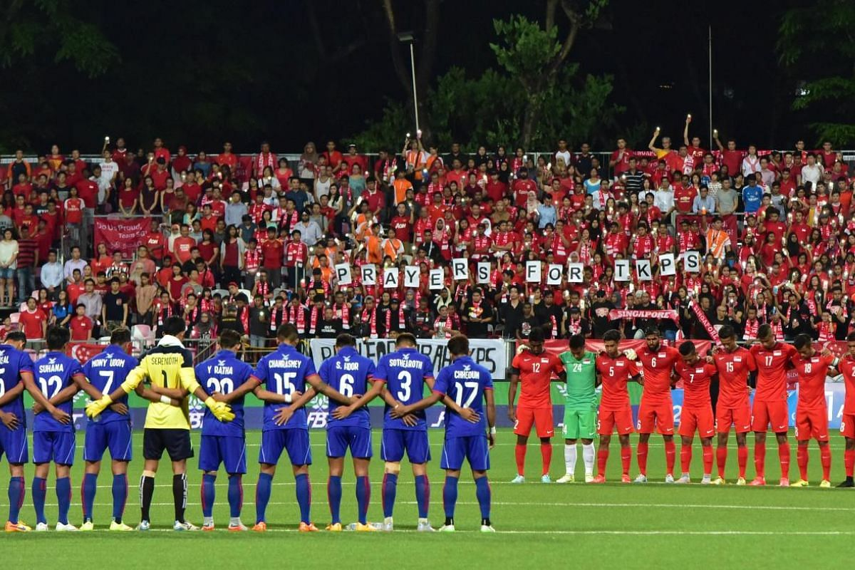 Teams from Cambodia (in blue) and Singapore (in red) observing a minute of silence as a mark of respect for the victims of the Sabah earthquake on 8 June, 2015.