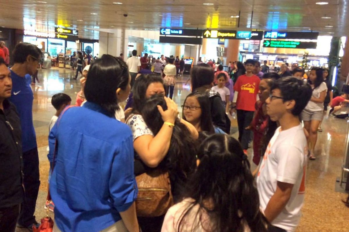 A relieved parent embracing her daughter after she arrived home safely at Changi Airport on June 6, 2015.