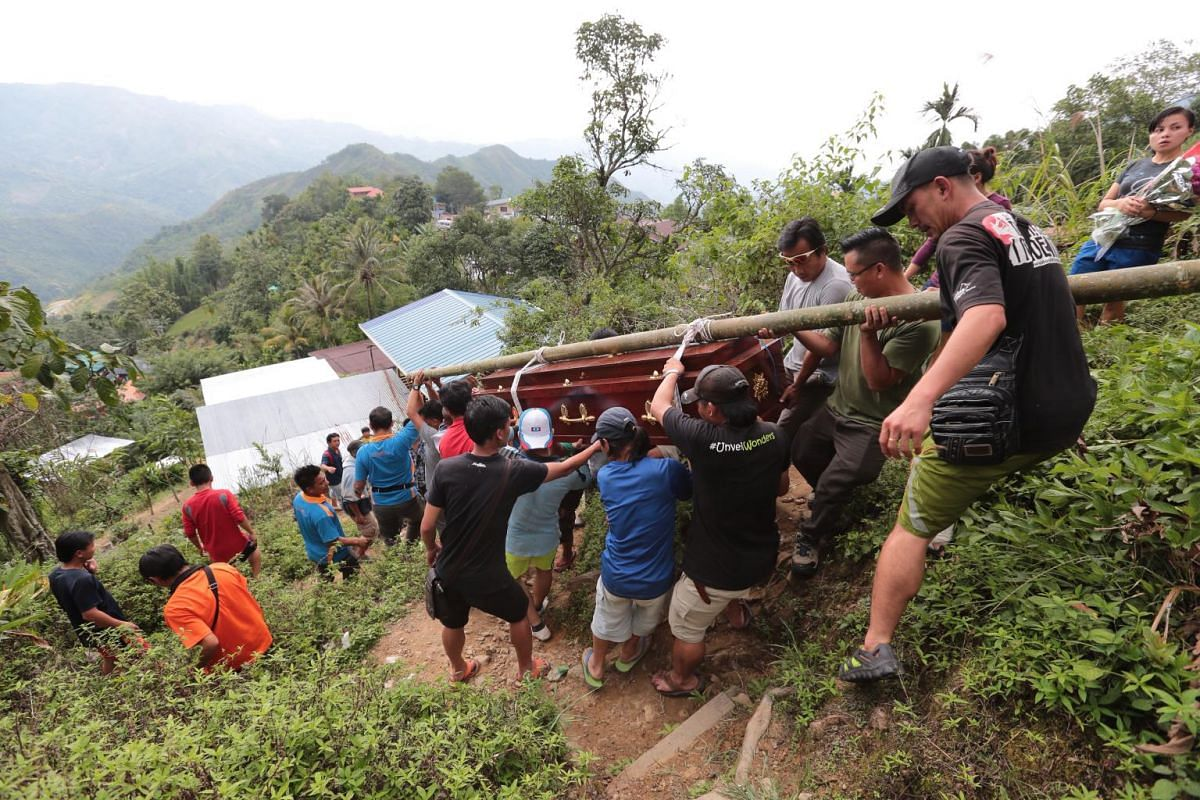 Mourners carrying Malaysian guide Robbi Sapinggi's body from his home in Kampong Kiau to the main road on June 7, 2015.. Mr Sapinggi has been hailed a hero after he lost his life  saving a tourist during the earthquake.
