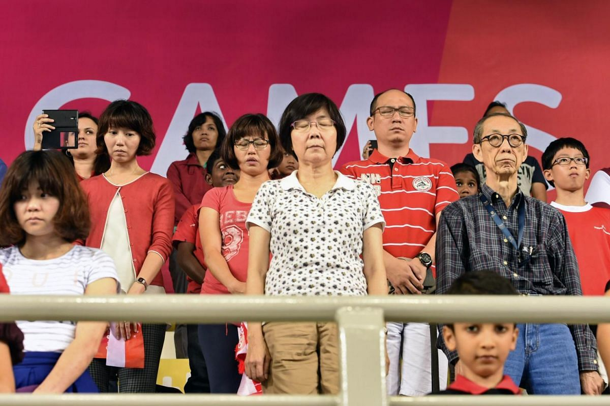 Spectators with their heads bowed observing a minute's silence before the start of the SEA Games gymnastics events at Bishan Stadium on June 8, 2015.