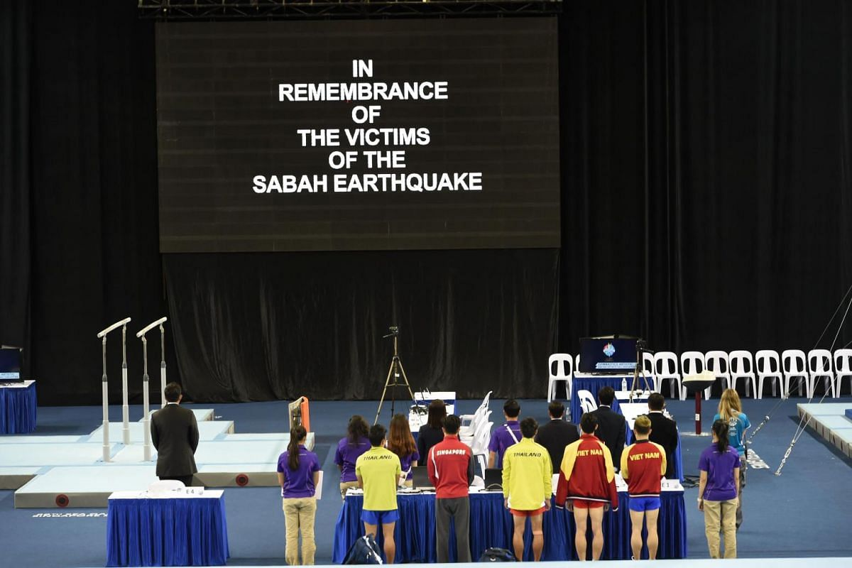 Participants pausing for a minute's silence at the start of the SEA Games gymnastic events at Bishan Stadium on June 8, 2015.