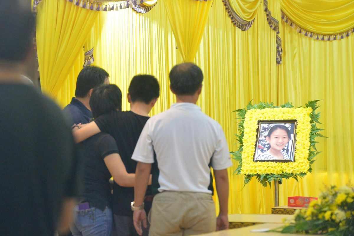 Tajong Katong Primary School student Peony Wee Ying Ping's father Alson Wee, older brother Chester and mother Luo Jin at her wake on June 7, 2015.