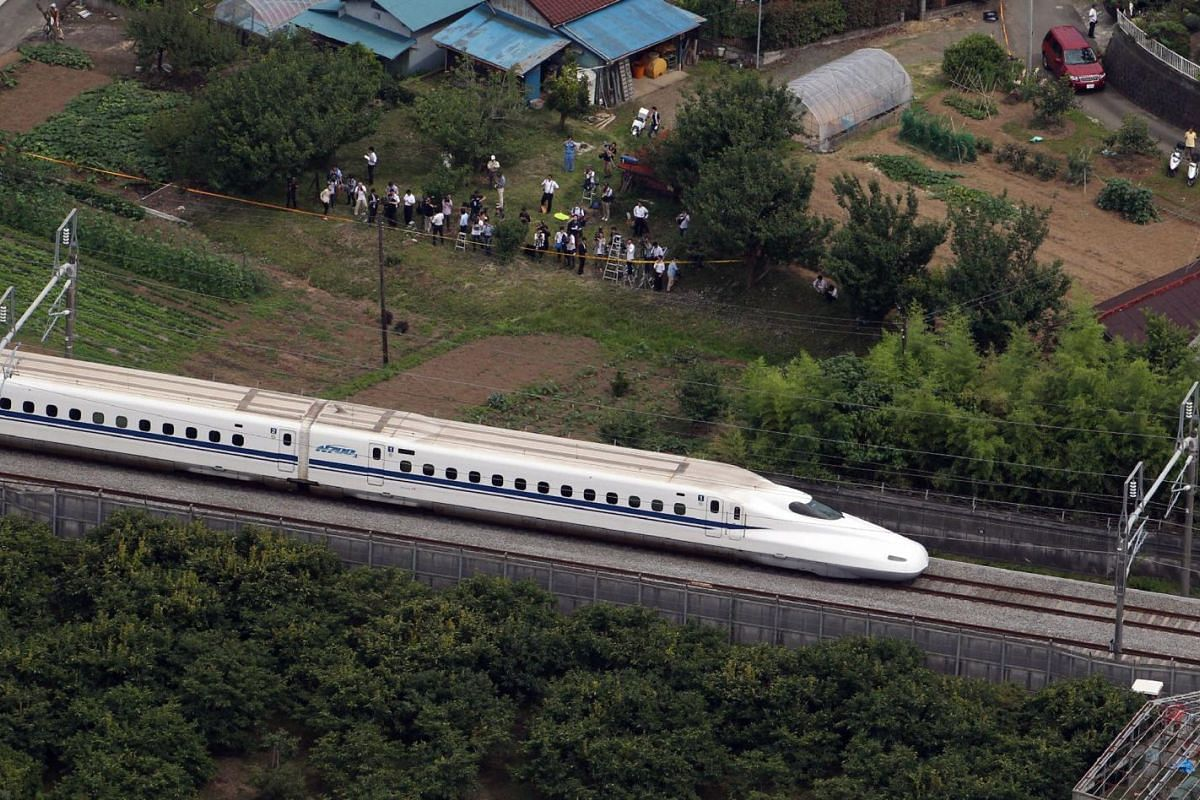 """A Nozomi 255 bullet train, or """"shinkansen"""", moving slowly toward Odawara station on June 30, 2015, after an apparent suicide attempt on board. A man set himself on fire on board the train, killing himself and one other person and injuring others."""