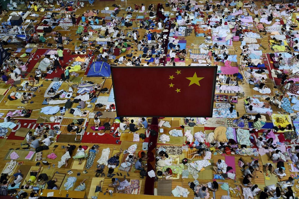 Students preparing to sleep on mats laid out on the floor under a Chinese national flag inside a gymnasium at the Huazhong Normal University in Wuhan, Hubei province, China, on June 29, 2015. More than 1,000 students slept inside the gymnasium to esc