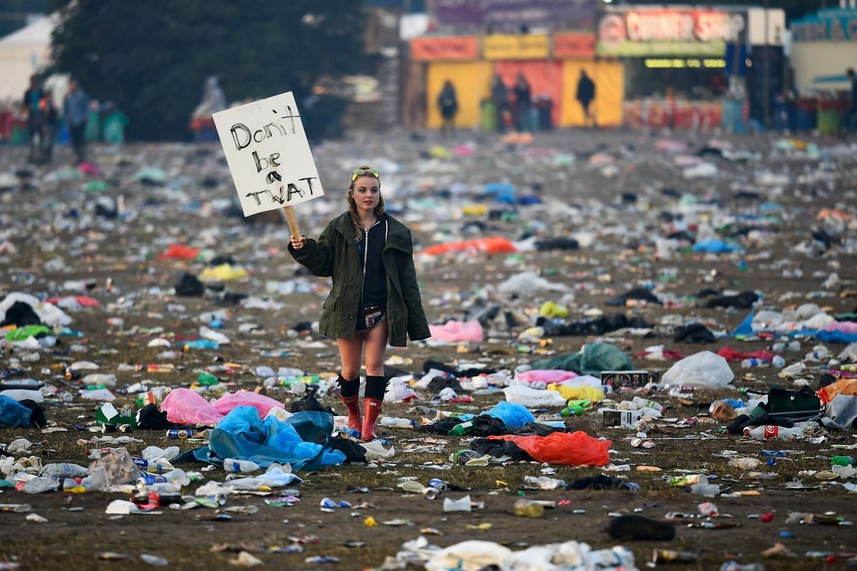 A reveller walking through rubbish in front of the Pyramid Stage as they leave Worthy Farm in Somerset after the Glastonbury Festival in Britain on June 29, 2015.