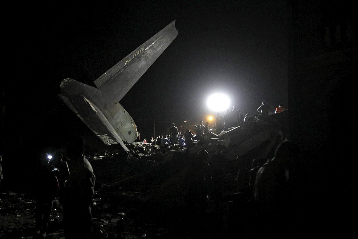Security forces and rescue workers searching the crash wreckage.