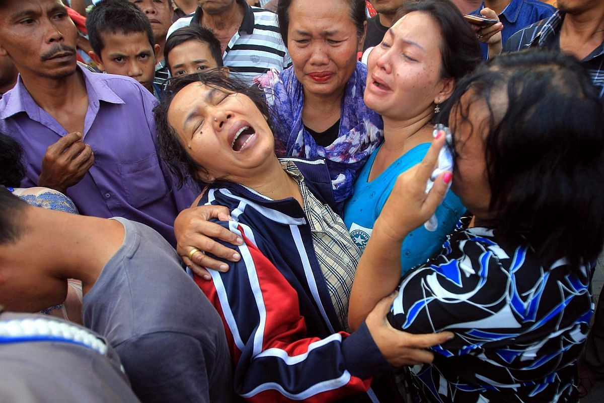 Relatives of one of the victims waiting for the body at a military hospital in Medan.