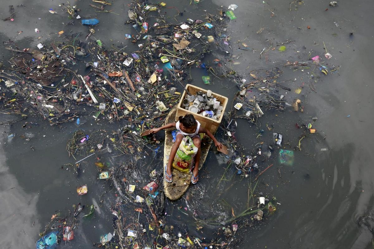 A girl sitting on a makeshift styrofoam raft as she collects recyclable material from floating garbage in a polluted river in Navotas city, north of Manila, on July 2, 2015.