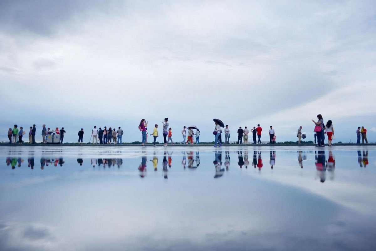 A group of tourists are reflected in the waters of the Songhua River in Harbin in north-east China's Heilongjiang province on July 1, 2015.