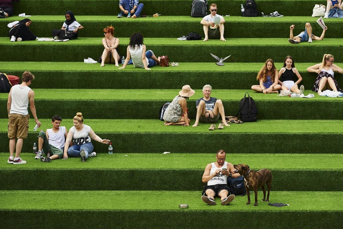 People enjoying the warm weather in central London on July 1, 2015. A blistering heatwave sweeping through Europe brought blackouts to France and fears of heat stroke for Wimbledon tennis fans.