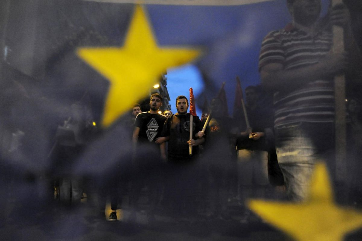 Anti-EU protesters are seen through a burned and torn European Union flag during a protest at the northern city of Thessaloniki, Greece July 1, 2015. A defiant Prime Minister Alexis Tsipras urged Greeks on Wednesday to reject an international bailout