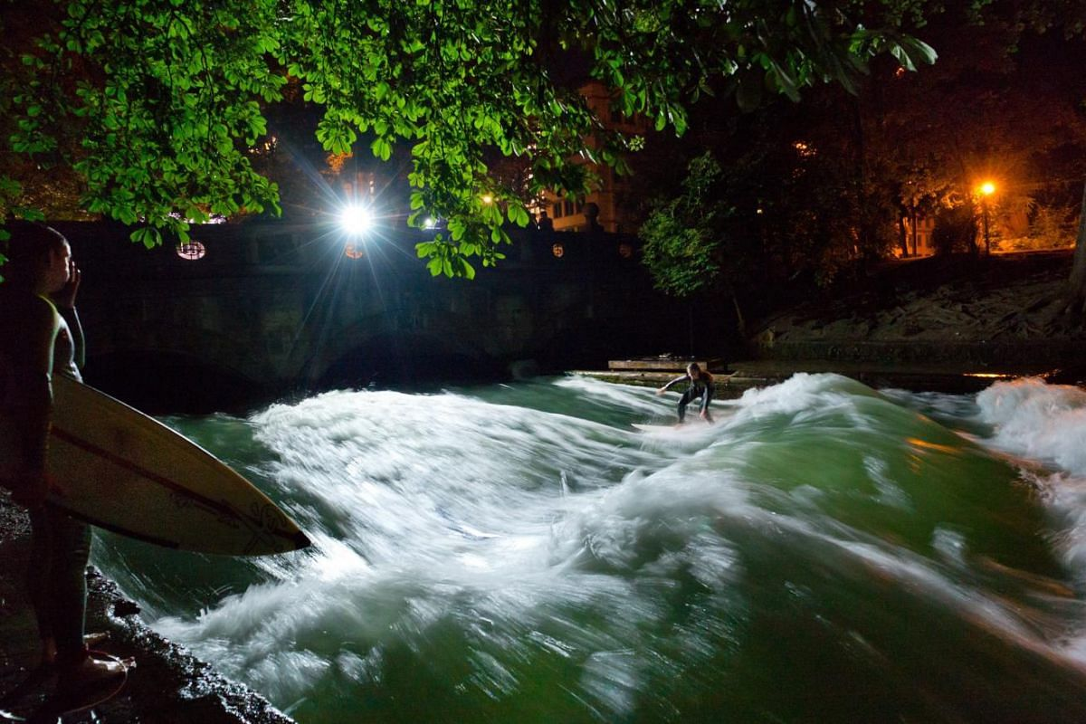 A woman taking part in floodlight night surfing on artificial waves on the man made stream flowing through the English Garden, Munich, Germany on the evening of July 2, 2015.