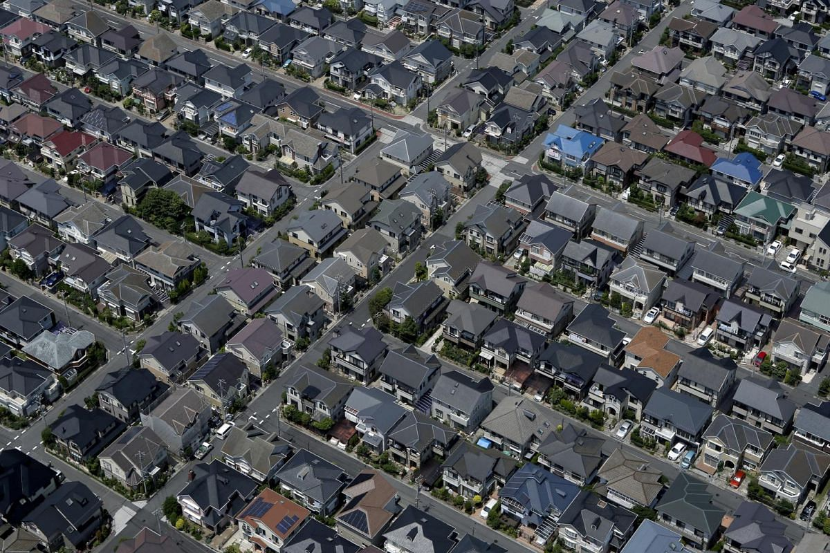 Residential buildings stand in this aerial photograph taken in Urayasu, Chiba Prefecture, Japan, on Wednesday, June 24, 2015. The Abe administration aims to cap increases in spending as it tries to rein in the world's heaviest debt load while sustain