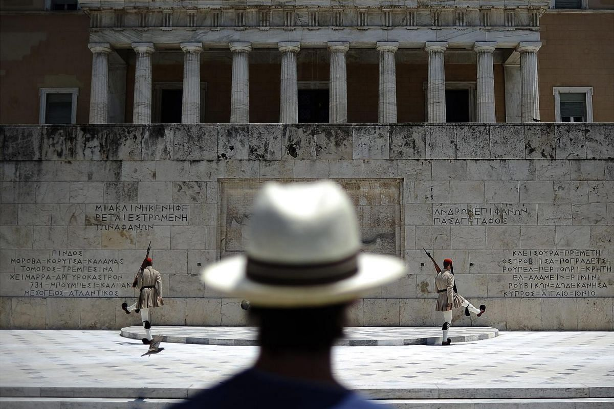 A tourist is watching the presidential guard in front of the Greek Parliament in central Athens, Greece, July 2, 2015. Greek Prime Minister Tsipras remained steadfast in his controversial plan to hold a referendum on the bailout demands of creditors.