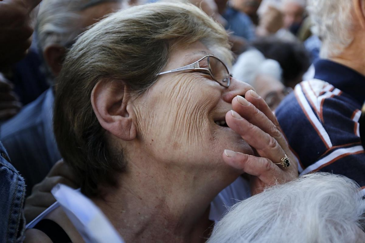 A pensioner crying as she tries to get inside a National Bank of Greece branch to collect her pension in Athens.