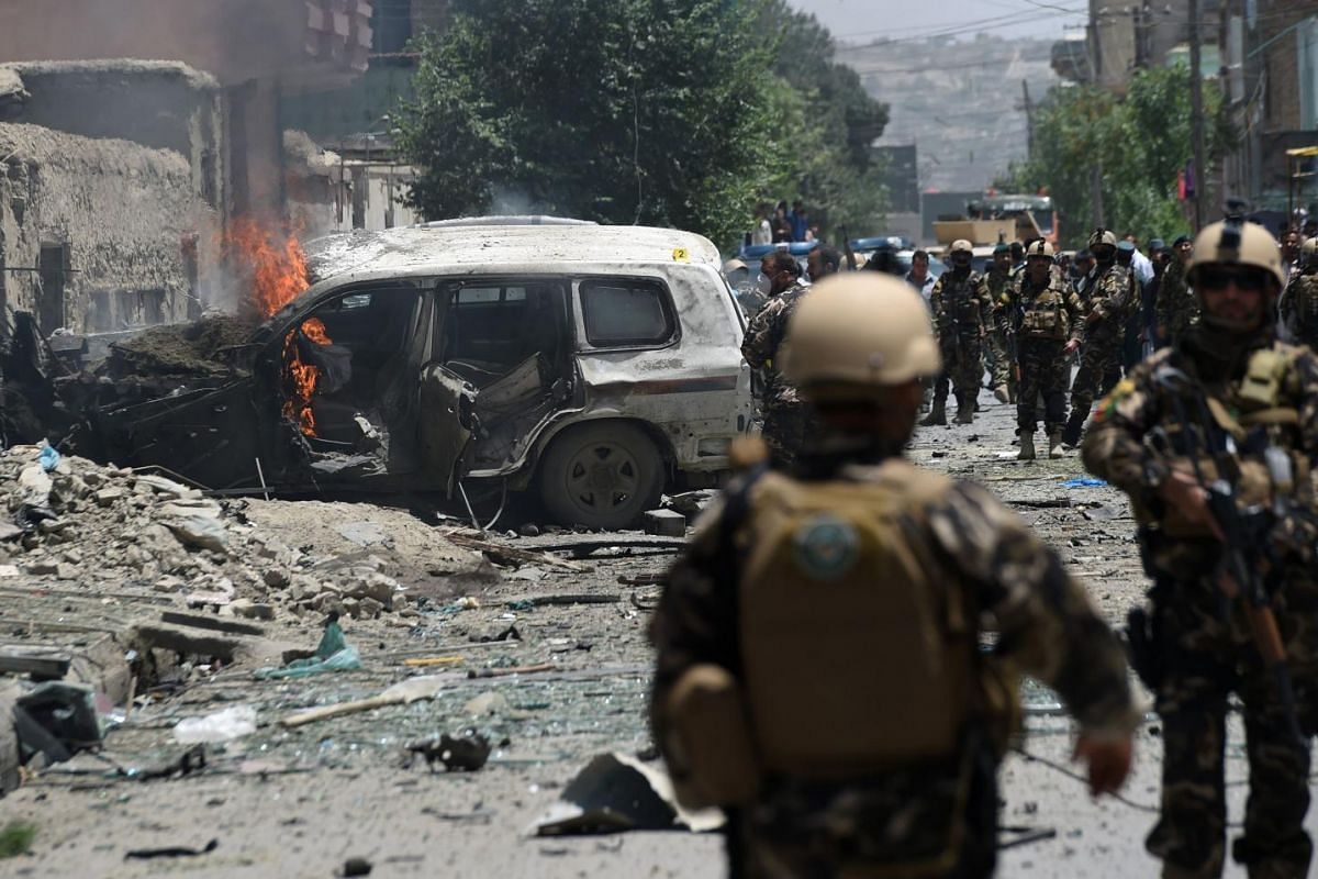 Smoke and flames rise from burning vehicles at the site of a bomb blast that targeted NATO forces in Kabul on July 7, 2015. A bomb blast targeted NATO forces in Kabul.