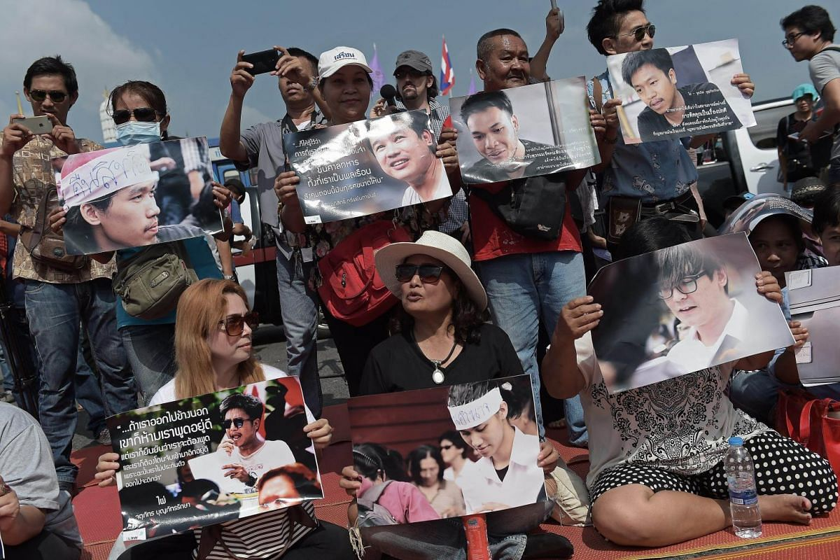 Supporters hold pictures of detained students as they take part in a protest in their support outside the cordoned-off military court where they appeared, in Bangkok on July 7, 2015. A group of 14 Thai students detained over a peaceful anti-coup rall
