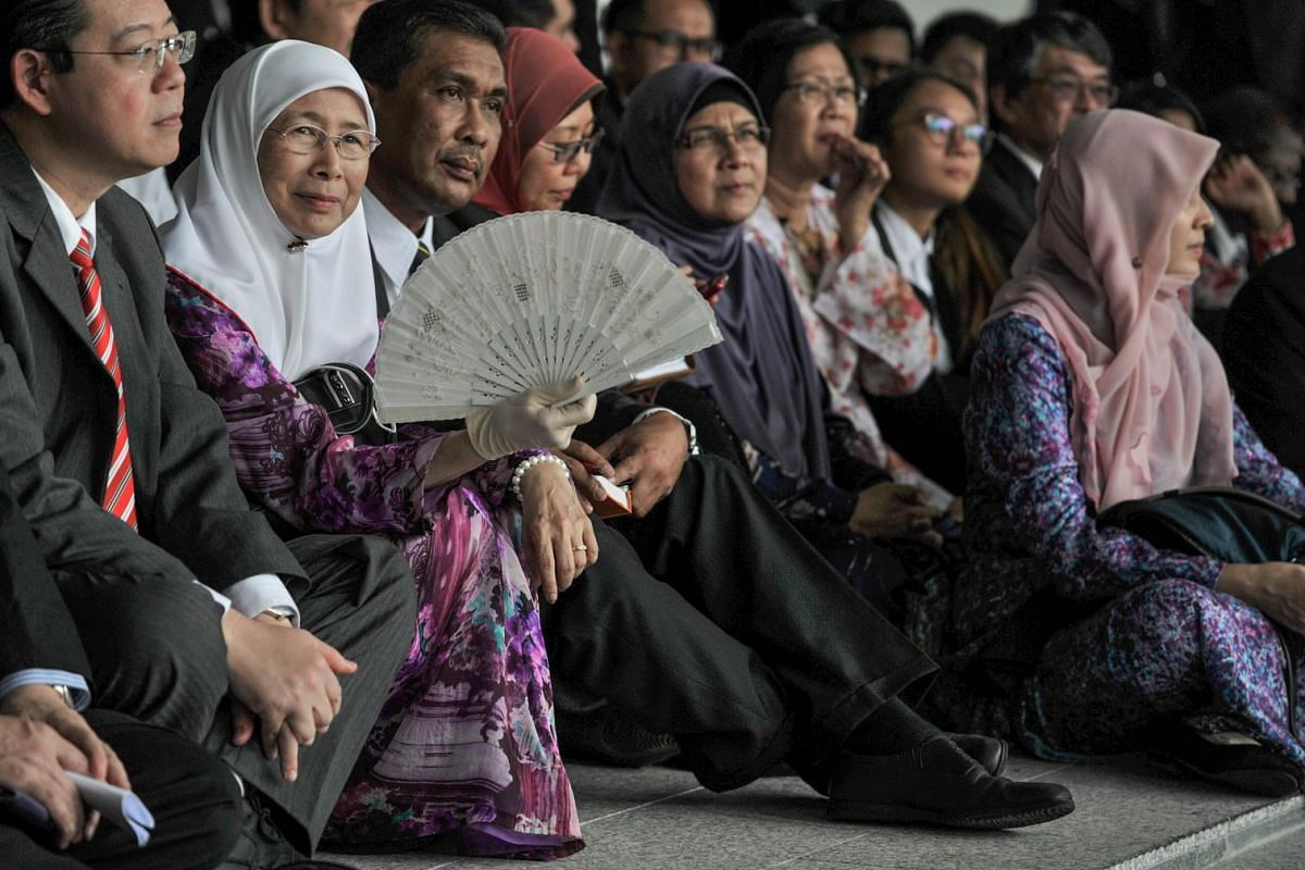 Malaysian opposition leader Wan Azizah (2nd L), the wife of jailed opposition icon Anwar Ibrahim, attending a sit-in with members of the opposition at the corridor of Parliament house in Kuala Lumpur on July 7, 2015, following allegations that a prob