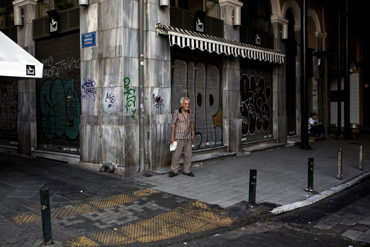 """A man stands next to meat market early in the morning on July 7, 2015 in Athens. Eurozone leaders will hold an emergency summit in Brussels on July 7 to discuss the fallout from Greek voters' defiant """"No"""" to further austerity measures, with the coun"""