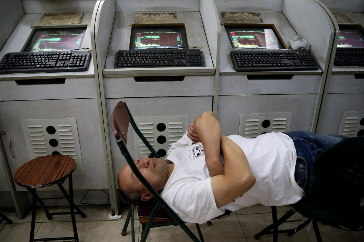 A stock investor takes a nap beside a line of computer screens showing stock prices at a brokerage house in Beijing city, China, 07 July 2015. China's shares dropped as the benchmark Shanghai Composite Index dropped 1.29 percent, or 48.78 points, to