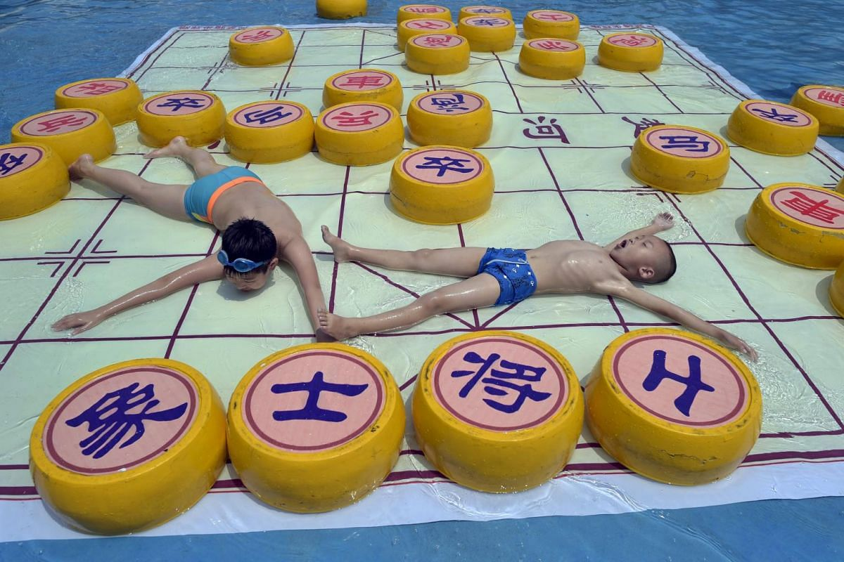 Children cool off on a 20 square meter Chinese chess board, at a water park in Chongqing municipality, July 7, 2015.