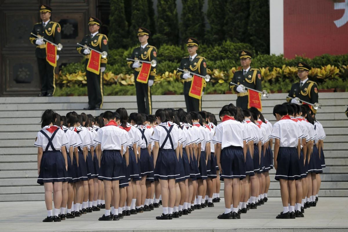 Students stand in silent tribute outside the Museum of the War of Chinese People's Resistance Against Japanese Aggression, near the Marco Polo Bridge on the outskirts of Beijing, July 7, 2015. With dioramas of heroic Communist soldiers and graphic pi