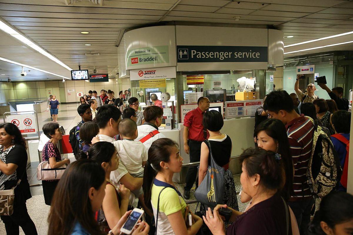 SMRT staff talking to commuters at Braddell MRT station.