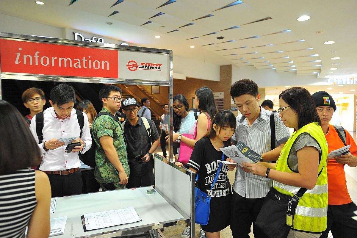 Commuters and SMRT staff at City Hall MRT station on July 7, 2015.