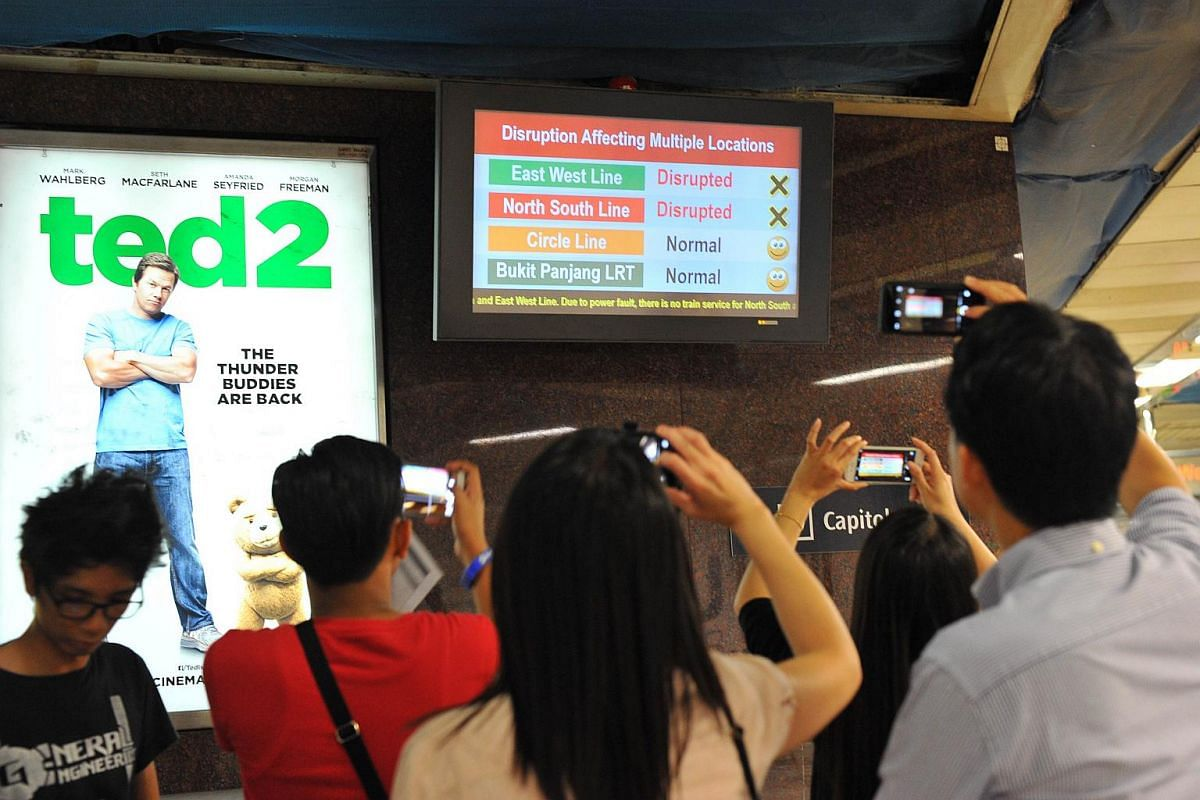 Commuters taking photographs of the signboard at City Hall MRT station.