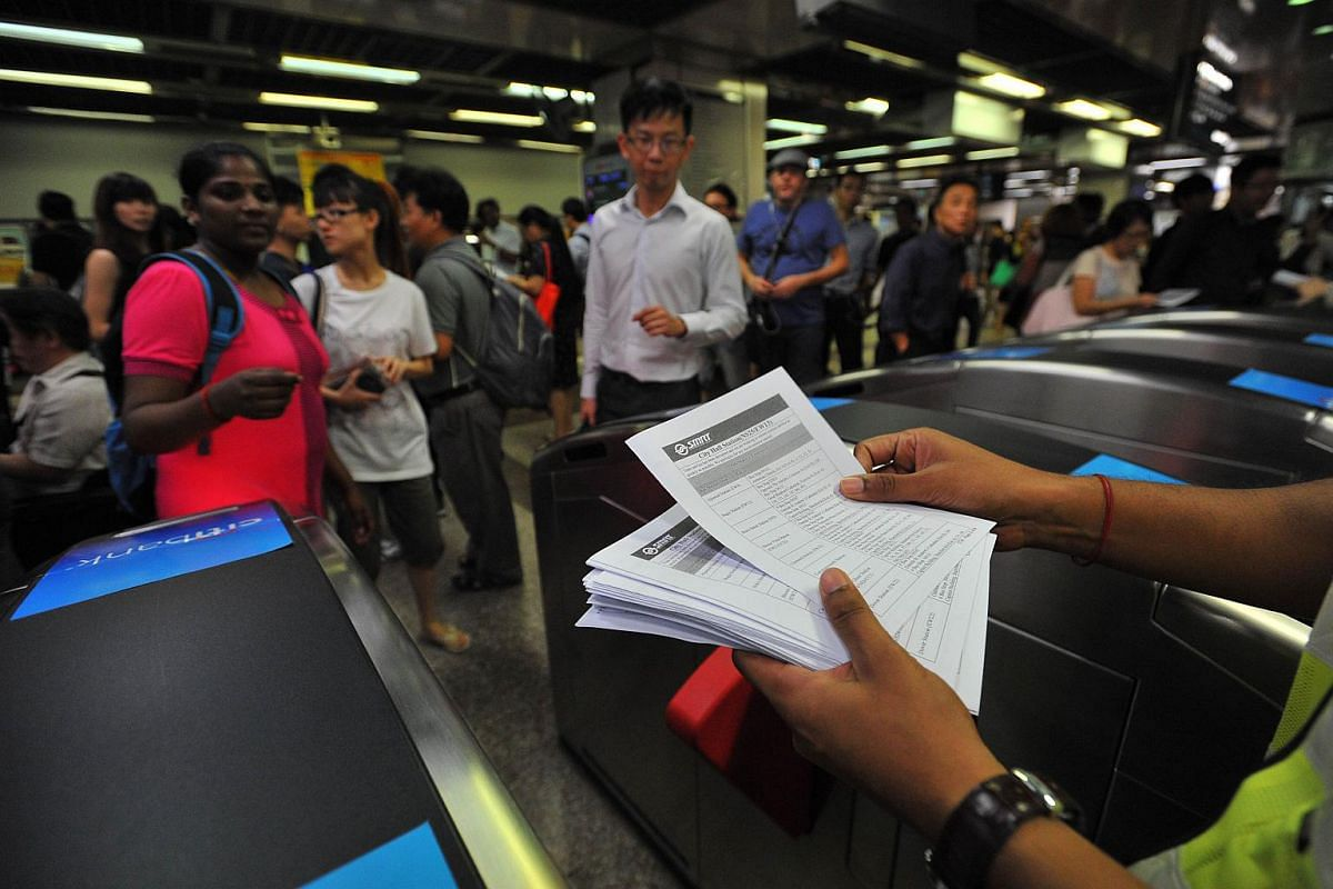 Staff handing out leaflets at City Hall MRT station during the MRT breakdown on July 7, 2015.