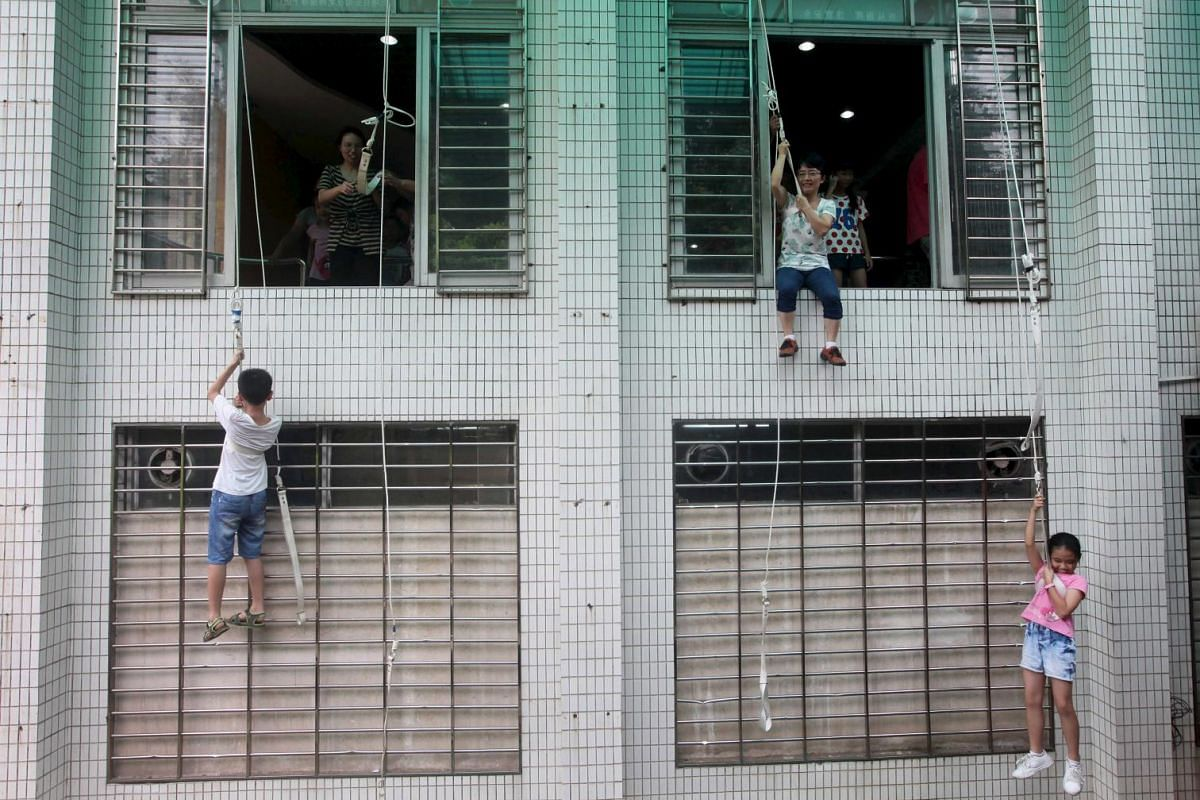 Children and parents rope down a building as they participate in a safety education activity to experience a fire escape, at a school in Guangzhou, Guangdong province on July 5, 2015.