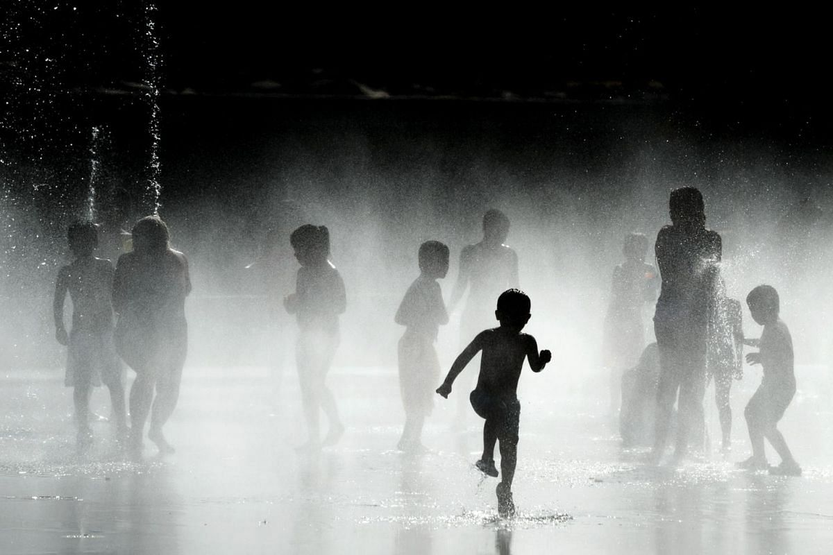 Children play with the water of fountains on the banks of the Manzanares river in Madrid on July 7, 2015. In Spain started on July 1, 2015 a new heatwave which will last for at least nine days and extend to the rest of Europe.
