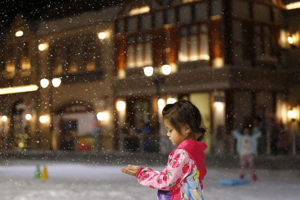 A little Thai girl enjoying artificial snow at Snow Town park in Bangkok, Thailand on July 7, 2015. Amid the heat, humidity and high temperatures of Bangkok, the newly opened Snow Town themed park attracts local and foreign tourists to escape from th