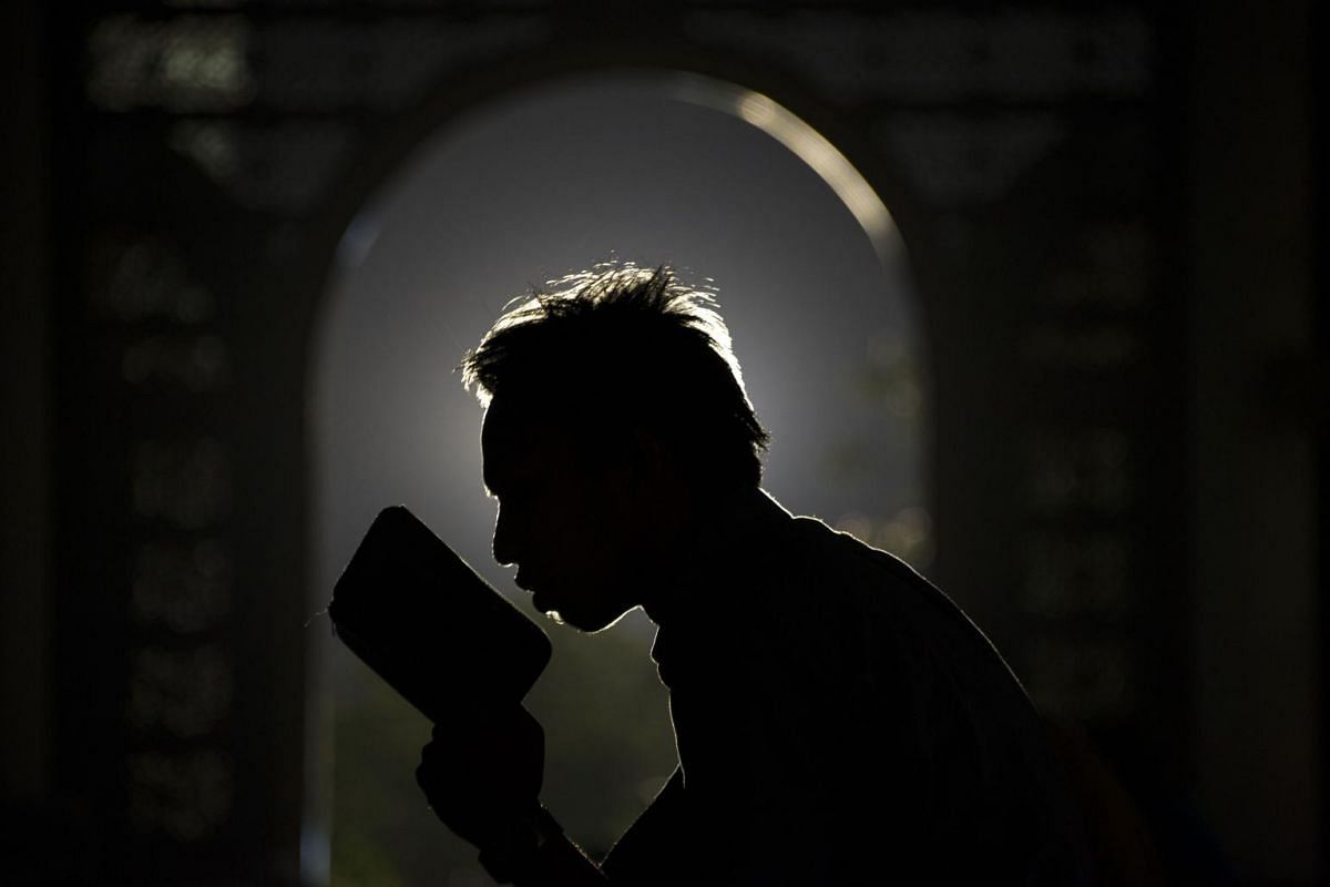 An Indonesian Muslim devotee prays over a Quran as the month of Ramadan continues at a mosque in Surabaya on the eastern Java island on July 8, 2015. Indonesia is the world's most populous Muslim country.