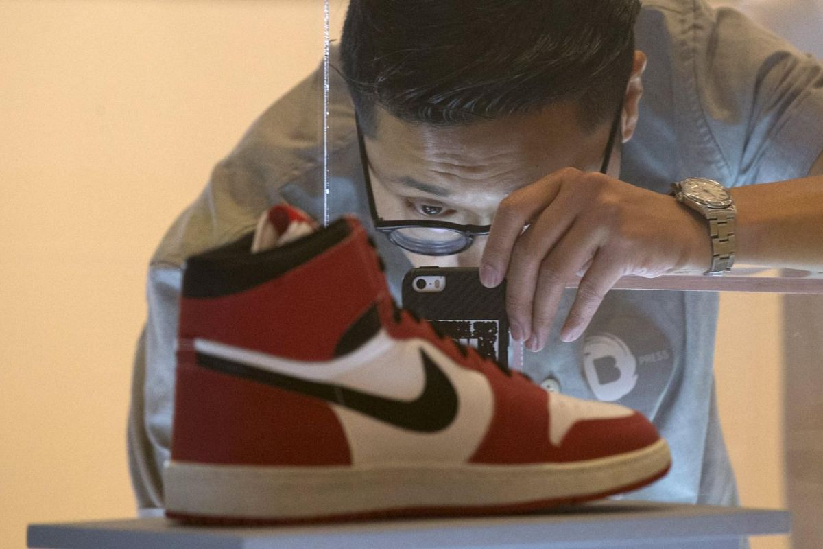 "A visitor photographs an Air Jordan I during a preview for ""The Rise of the Sneaker Culture"" exhibit at the Brooklyn Museum in the Brooklyn borough of New York, July 8, 2015."