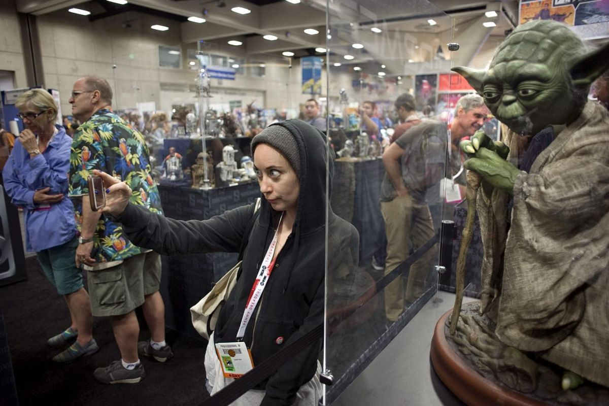 Ayelet Bick takes a photograph of herself next to a Star Wars figure during the preview evening of Comic-Con 2015 in San Diego, California, USA, July 8, 2015. Comic-Con opens on July 9, 2015.