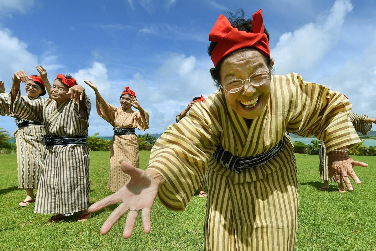 An elderly women troupe of singers and dancers from Kohama Island in Okinawa wearing traditional local costumes perform at a herb garden on Kohama Island, Okinawa Prefecture. They joke about knocking on heaven's door, but a Japanese 'girl band' with