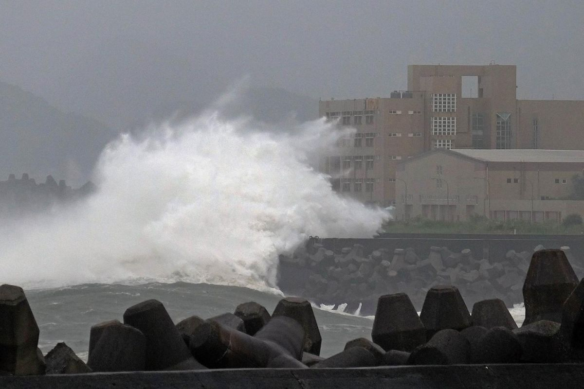 Giant waves crash into the coastline next to National Taiwan Ocean University (R) in Keelung as Typhoon Chan-hom brings rain to northern Taiwan on July 10, 2015. Taiwan was bracing for fierce winds and torrential rains on July 10 as Typhoon Chan-hom