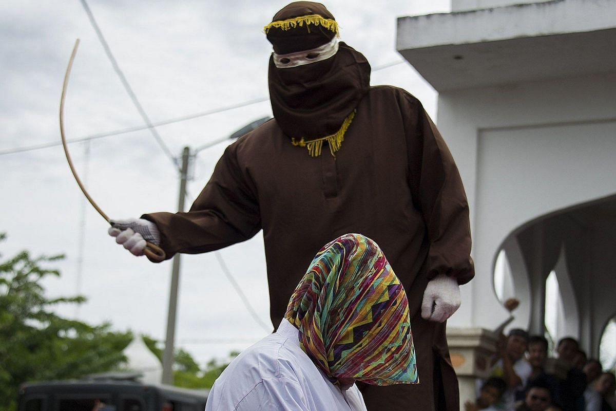 """An Acehnese woman convicted of """"immoral acts"""" being lashed by a hooded local government officer during a public caning at a square in Banda Aceh, Aceh province, last month."""