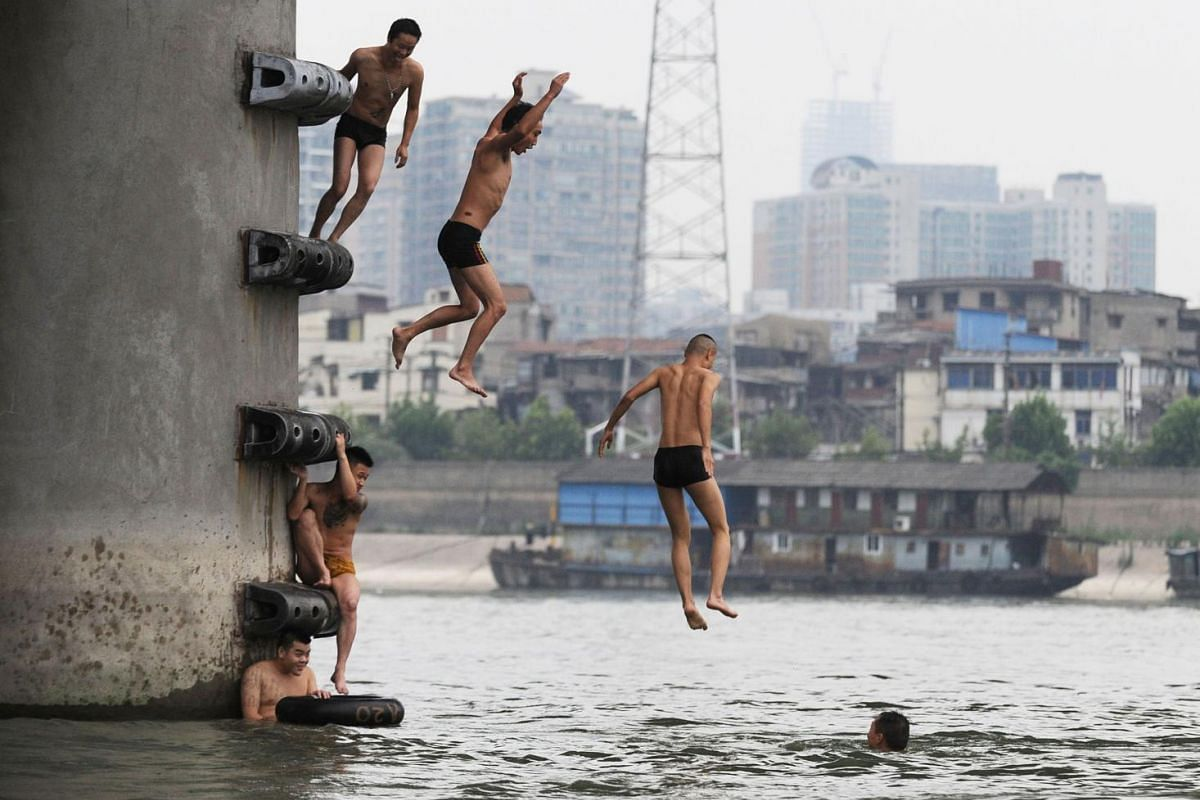 People jumping into the Han River to cool off as a heat wave hits the area in Wuhan, central China's Hubei province on July 14, 2015.