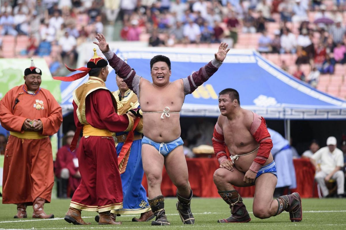 Mongolian wrestler Enkhtuvshingiin Oyunbold (C) celebrating his victory in the seventh round of the National Naadam Festival at the Central Stadium in Ulan Bator.