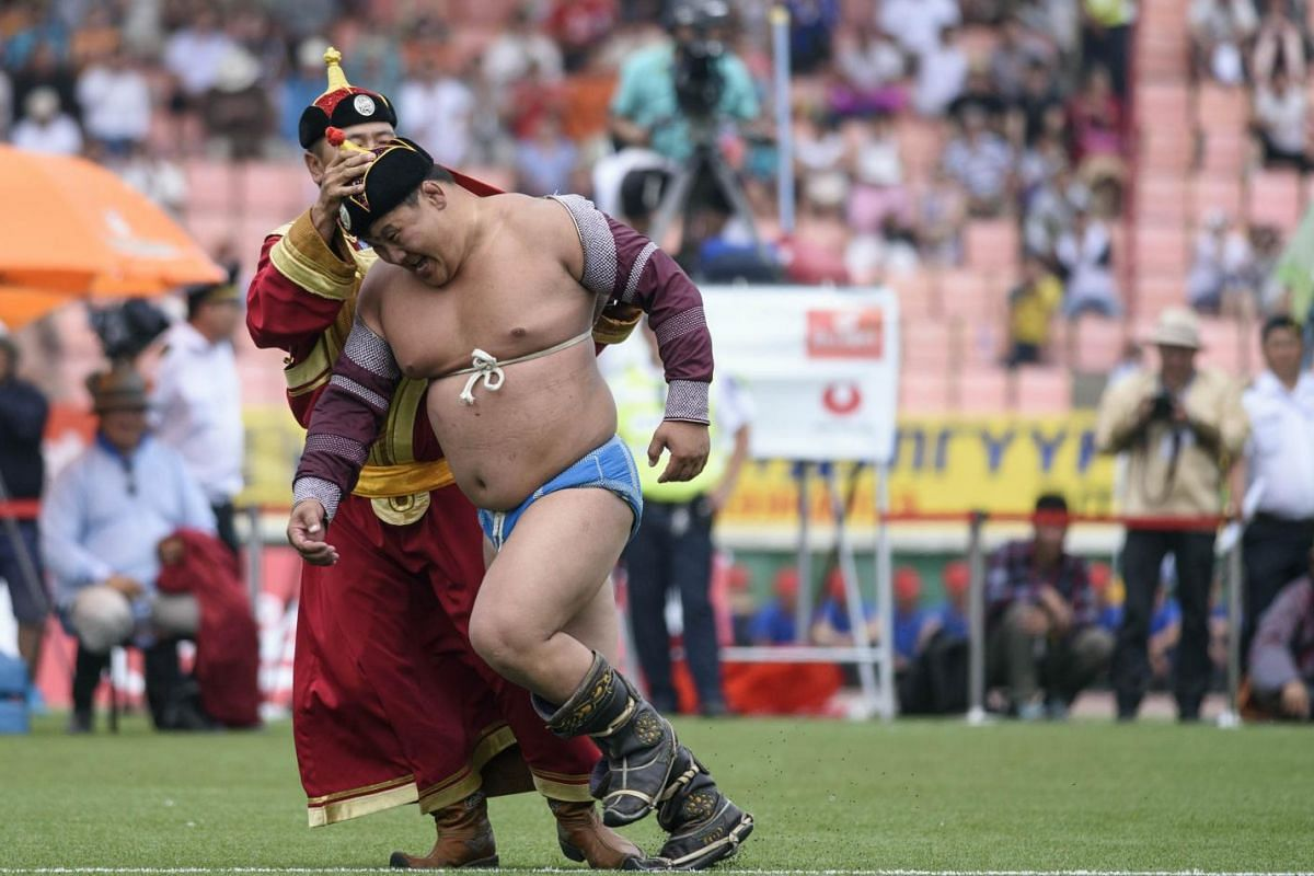 Mongolian wrestler Enkhtuvshingiin Oyunbold (front L) receiving his hat after winning his bout in the fifth round of the National Naadam Festival at the Central Stadium in Ulan Bator.